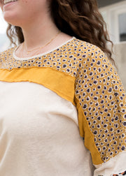 Our cream, mustard and pattern block oversized plus size top paired with jean shorts.