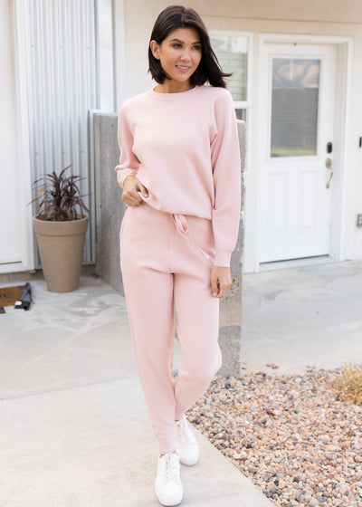 Our light pink, sweater and jogger matching set paired with tennis shoes.