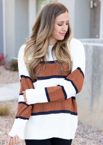 Nichole is wearing our white, tan and black stripe sweater paired with black leggings and white sneakers!