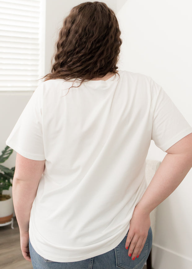Our white, 'wander' plus size graphic  t-shirt paired with jeans.