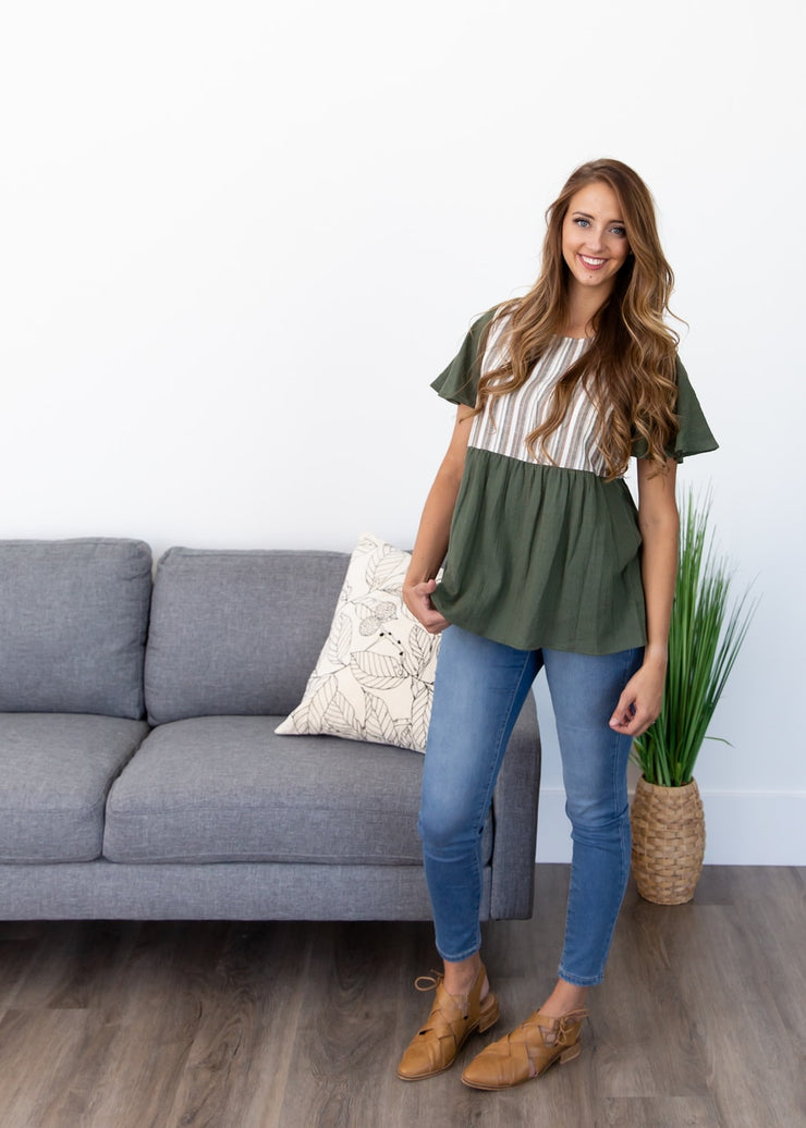 Lexi is wearing our olive pattern block top paired with jeans and flats!