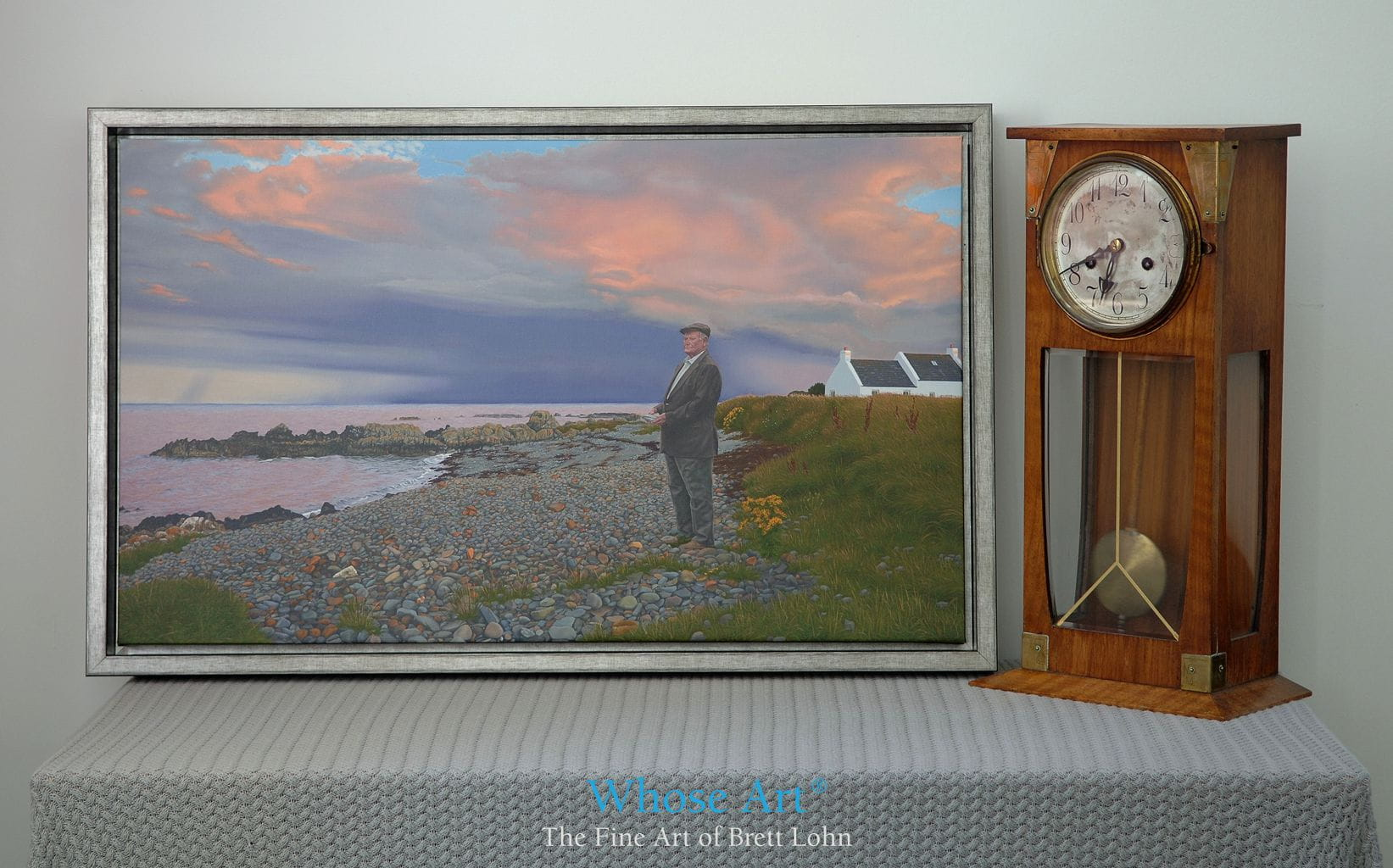 Framed canvas art picture in a hotel room with tasteful interior decoration of a clock and hotel table. This art for hotels is an oil painting of a beach.