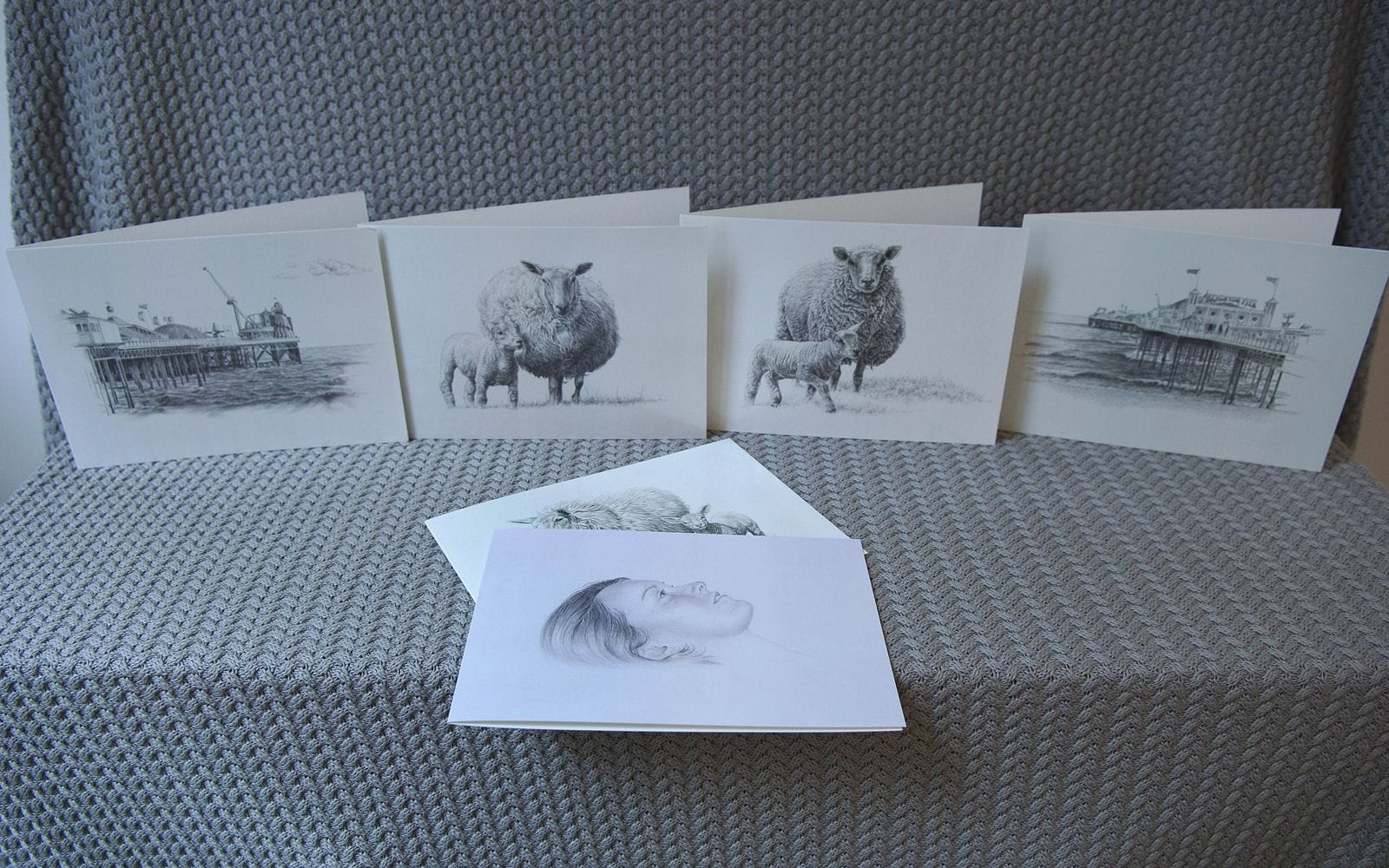 A selection of black & white greeting cards arranged on a table. Some of the greeting cards feature pencil drawings of sheep.