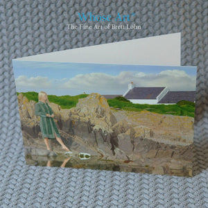 Art of Ireland greeting card of a woman in a green coat, standing on the Irish coast with her foot pointed toward a stone.