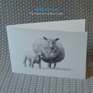 Black & white greeting card of a detailed pencil drawing of a sheep with a lamb leaning against it. Card is blank inside