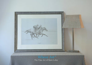 Black and white horse print framed in silver, showing two horses galloping with jockeys on board. The lead horse is a grey.