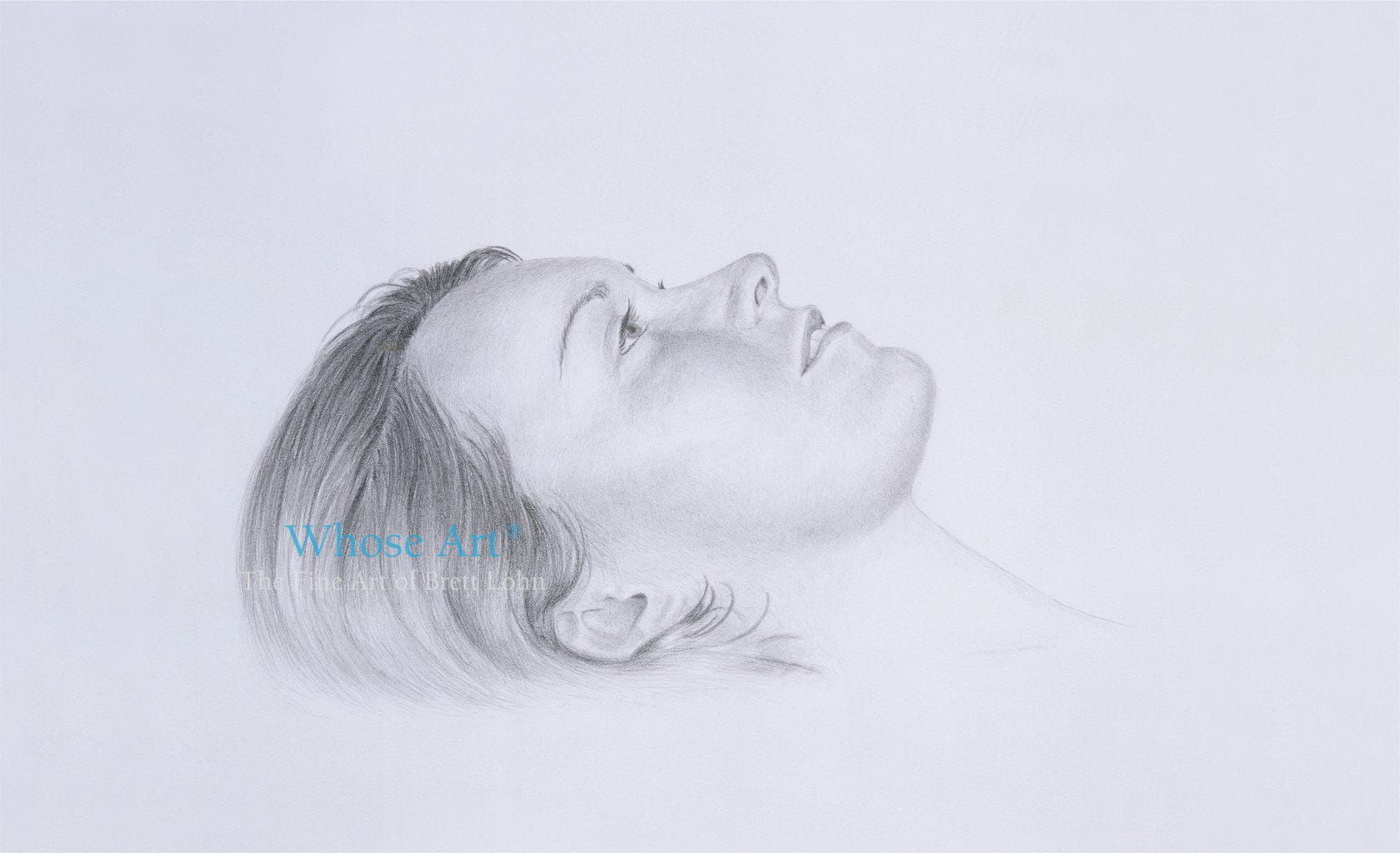 Black and white wall art drawing showing the face of a girl, shaded in pencil, lying down but looking upwards, daydreaming.