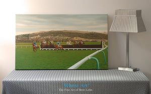 Canvas wall art depicting Cheltenham Racecourse during a National Hunt meeting. Horses jump the 13th fence and race home.