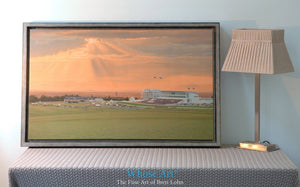 Canvas wall art of a dramatic sunset over Epsom Downs racecourse. The Canvas art print is framed silver and rests on a table.