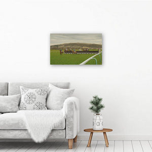 Canvas wall art print of a horse racing painting. The horse art print hangs on a white wall above an armchair and table.