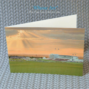 Derby art card with a horse art painting of horse racing at epsom downs racecourse on the front. The card sits on a table.