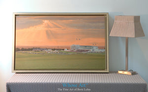 Epsom racing wall art print of a horse race beneath a stormy sunset sky in July. Framed in gold & leaning against a wall.