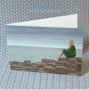 Fine art card of a painting depicting the Giant's Causeway & a young lady in a green velvet coat sitting on the stones