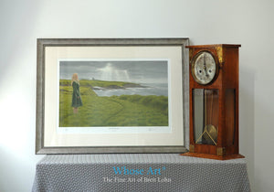 A framed art print of a mystical art scene showing a woman on a grassy cliff with a castle behind her, beneath a stormy sky.