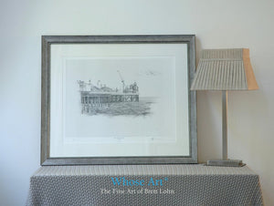 A black and white art print framed in silver, showing a pencil drawing of the Palace Pier in Brighton with the fairground on view