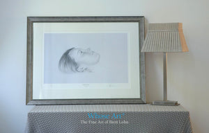Framed black & white wall art picture of a drawing of a girl's face as she lies daydreaming. Drawn in pencil & framed silver.