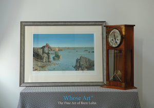 A framed narrative art print, resting on a table, showing a man on the Irish Coast, skimming a stone into the rippling water.