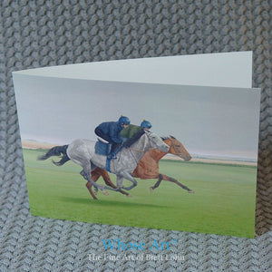 Galloping horse art greeting card on a table. The picture on the greeting card is of two racehorses galloping in training
