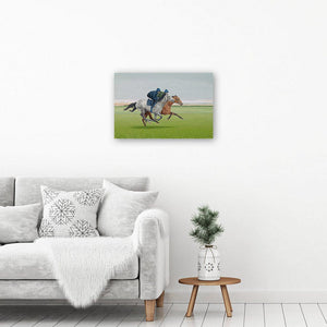 Canvas wall art print of a painting of galloping horses. Picture hangs on a wall above an armchair.