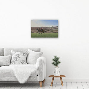 Galloping horses art print of a painting of two horses on the gallops in the morning. Picture hangs above a table & armchair.