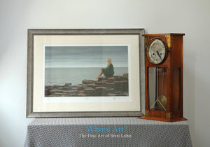 Framed Art Print sitting on a table showing an oil painting of a lady seated on the Giant's Causeway on an overcast day.