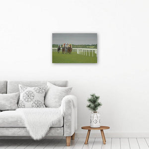 Horse racing art canvas print of a painting of racehorses running under a dramatic grey sky. The canvas print hangs on a wall