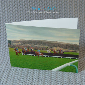 Horse racing greeting card featuring a painting of horses jumping at Cheltenham Racecourse with Cleeve Hill behind them