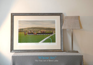 A framed horse racing print showing a painting of racing at Cheltenham Racecourse, framed in silver in an interior decor room