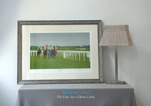A Framed Horse racing art print of a painting of horses racing at Epsom at an evening meeting. In an interior design setting.