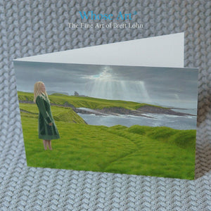 Irish art card of a painting of a lady in Mullaghmore standing in front of a County Sligo castle. The card stands on a table.