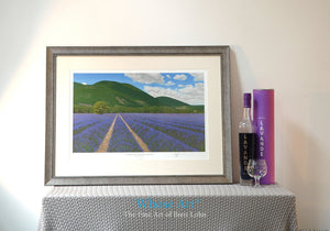 Framed art print of a lavender field painting set in the south of France. The Framed art print is resting on a table by a lamp