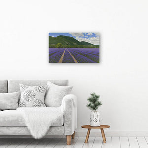 Canvas picture printed from an oil painting of lavender fields. The Art print hangs on a white wall above a table & chair.
