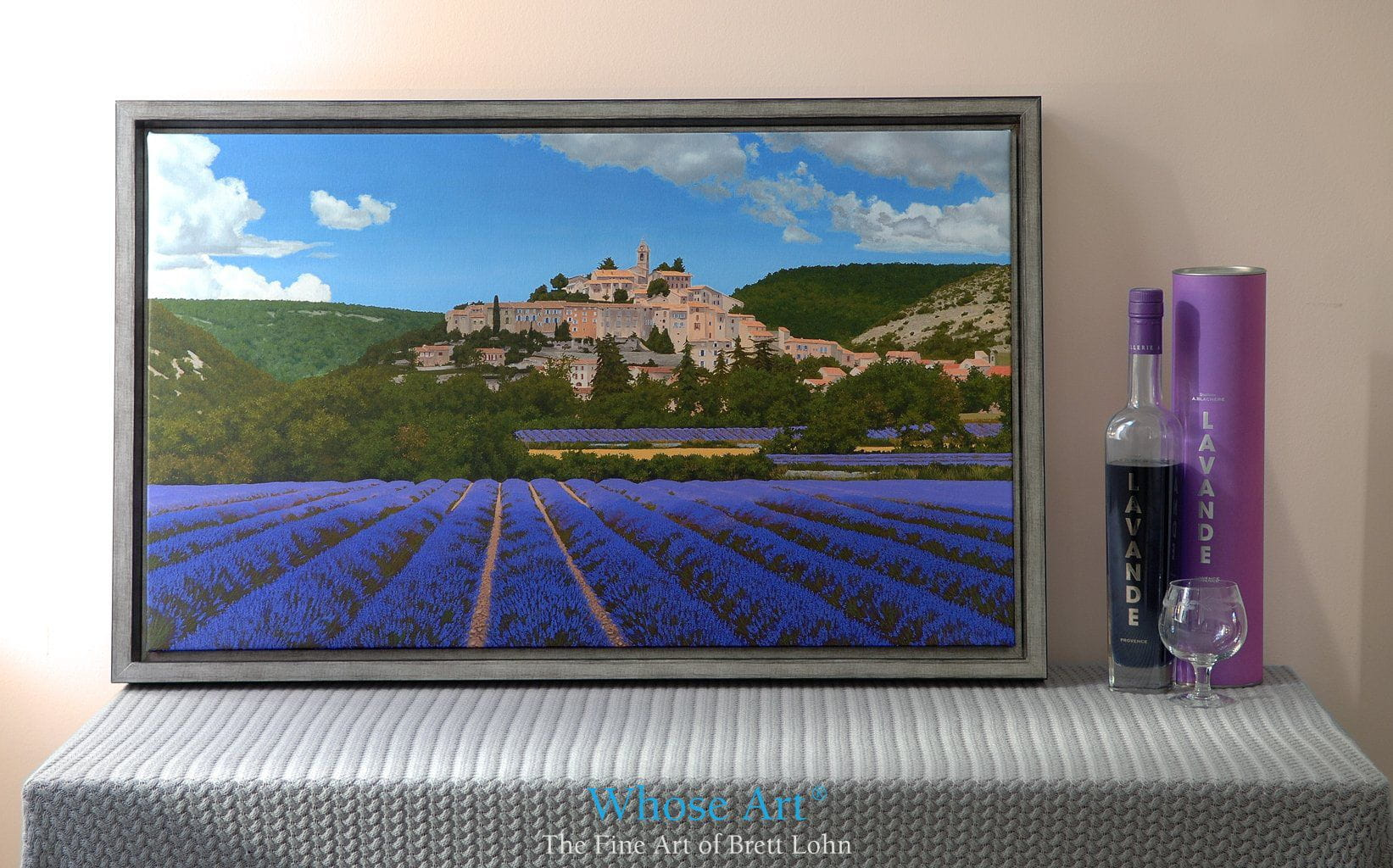 Canvas art print featuring a painting of a village nestling in a Lavender field in Provence, France. The print is framed.