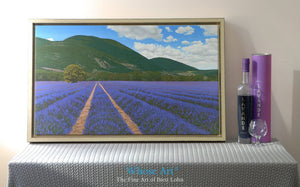 Lavender wall art canvas depicting French lavender fields in Provence. Canvas print is framed and sitting on a table by a lamp
