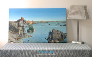 Narrative canvas wall art print from an oil painting telling a story of an old man by the sea. Canvas print rests on a table