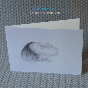 Pencil greeting card of a drawing of the head of a young woman who is daydreaming. The greeting card stands on a table