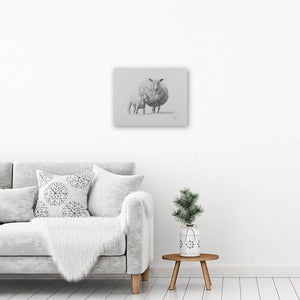 Sheep art canvas print hanging on a white wall above an armchair and a table with a plant on it. Canvas art print of a lamb.