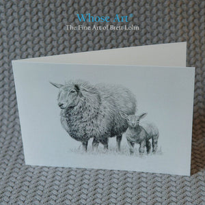 Sheep greeting card standing on a table. The greeting card shows a drawing of a protective sheep & a spring lamb together