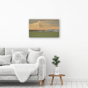 A beautiful sunset painting reproduced in a canvas art print hangs on a white wall above a coffee table by a chair.