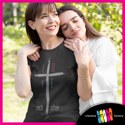 two women hugging wearing a shirt that says love each other