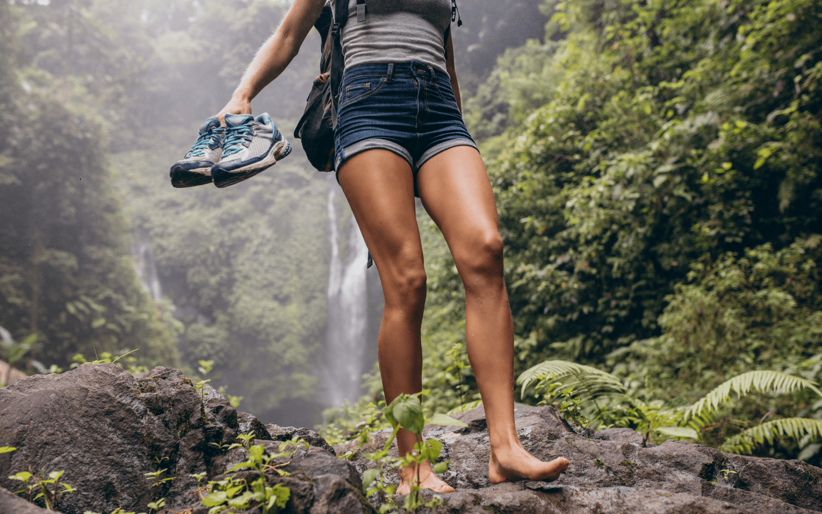 woman walking barefoot with shoes in hand