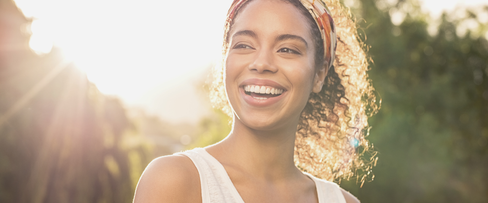 woman smiling with sunshine behind her
