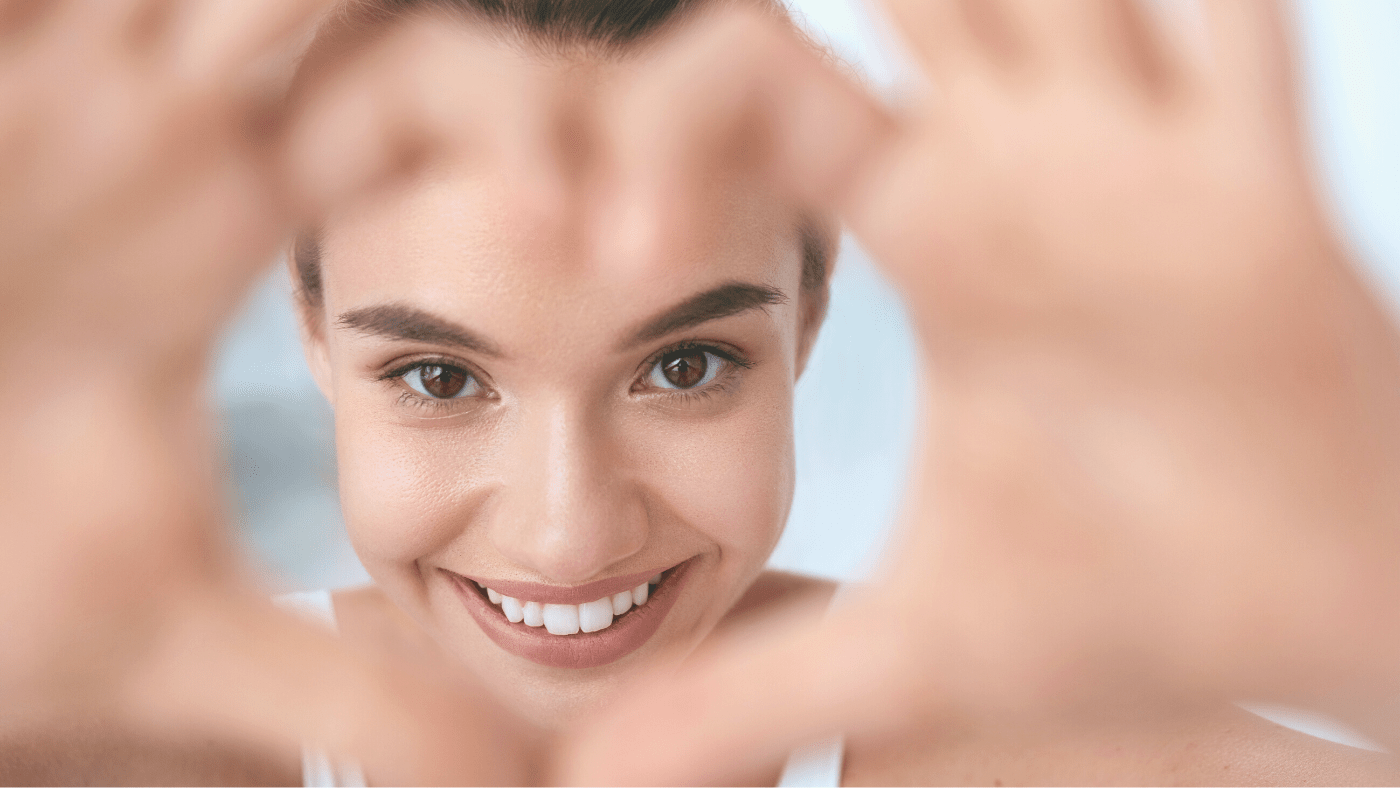 woman smiling inside of blurred heart shaped with her hands