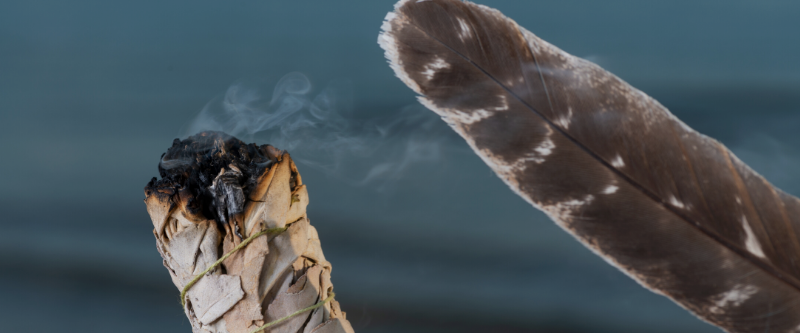 feather blowing burning sage to cleanse holistic skincare