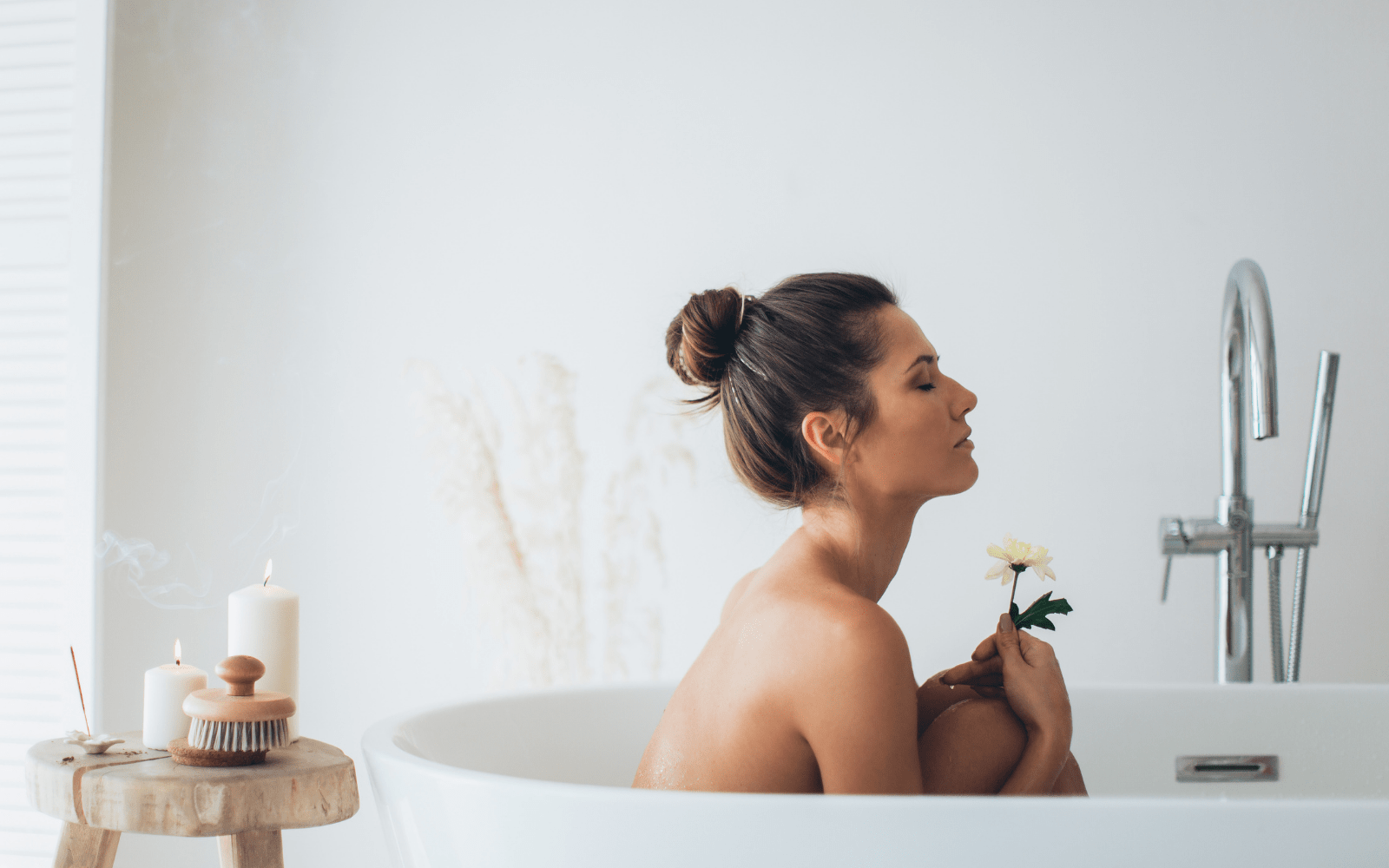 woman sitting in bath holding a flower with incense stick behind her