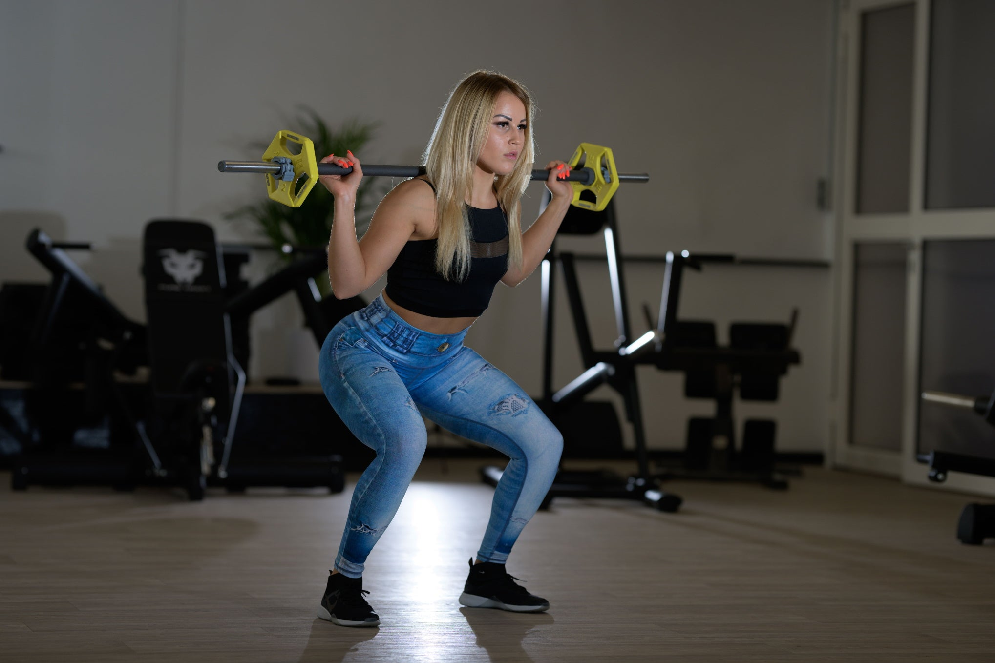 Model with barbell on the shoulders in denim jeans leggings style by Athletics Wear