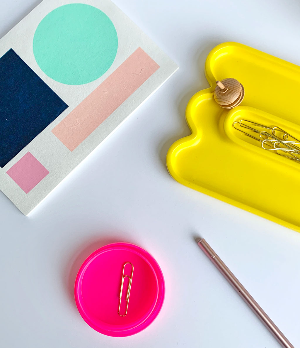 bright, colorful desk supplies like a notebook, yellow desk tray, hot pink paper clip holder