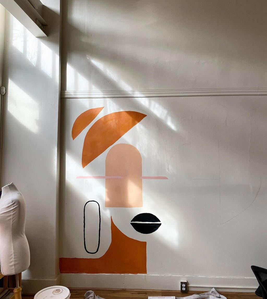 a mural painted on the wall, in oranges and peaches