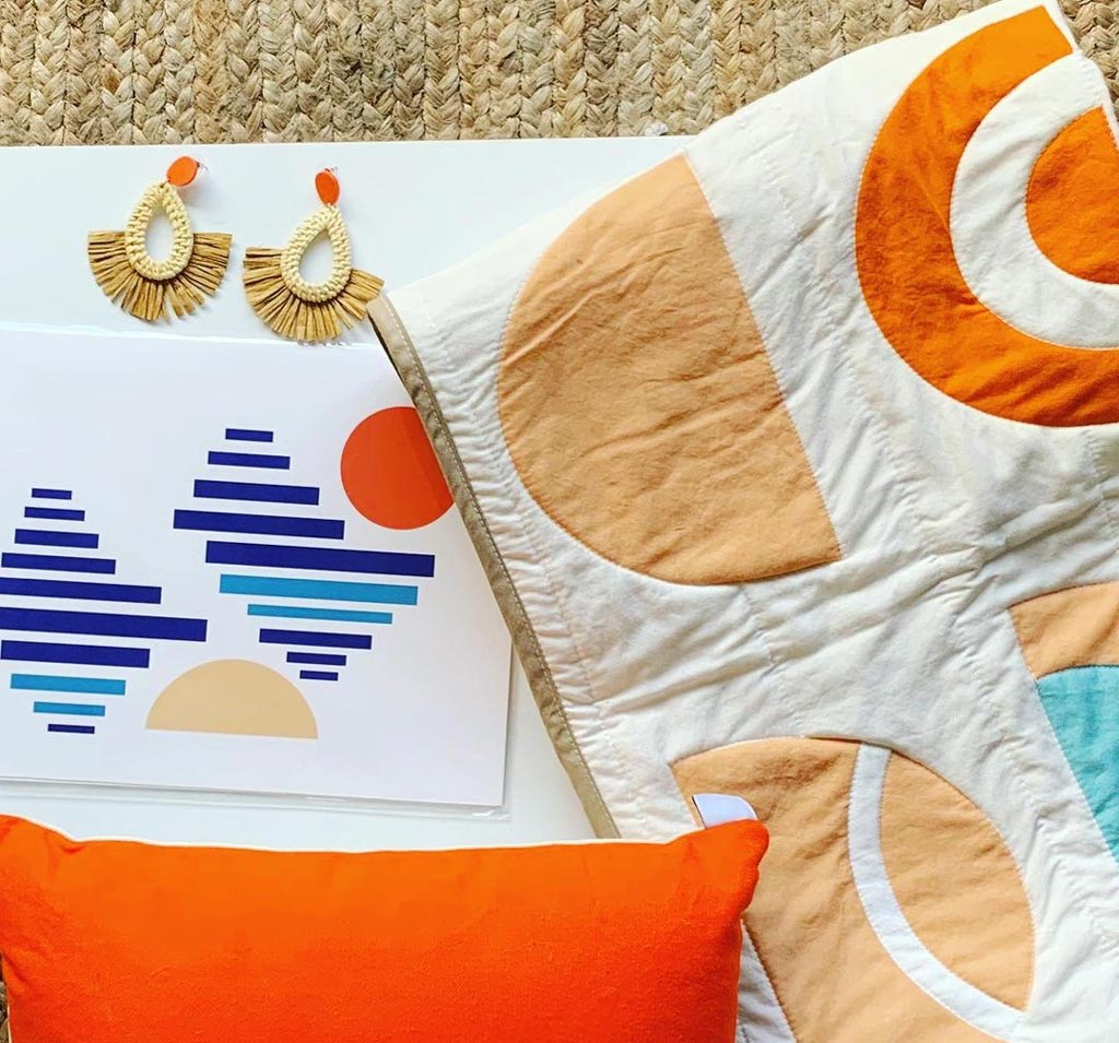looking down onto a grouping of objects: a quilt with orange designs on it, and orange cushion, a little piece of artwork with oranges and blues