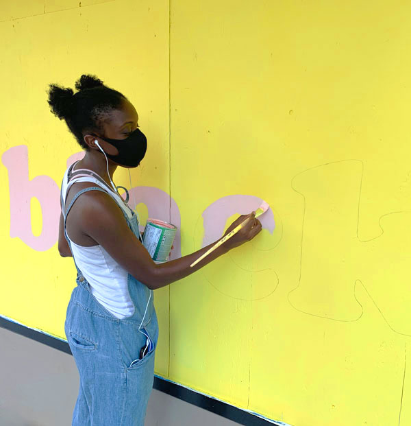 "Christine Miller, painting the word ""black"" in bold, sunny yellow and pink"